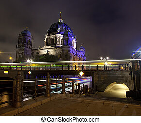 Light trails from a bus and a boat with the Berliner Dom in the background.