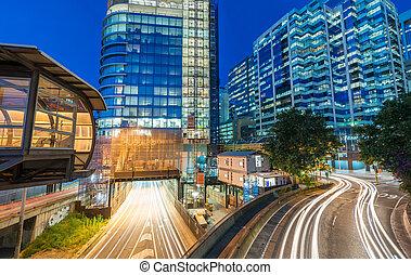 Light trails of cars speeding up along modern city