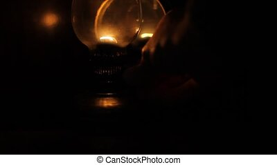 In a dark room, a person makes more light using the old gas lamp.