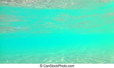 Light waves underwater near the sandy shore on a clear sunny day, Red Sea, sandy bottom. Slow motion Standard movement.