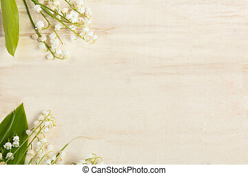 Light wooden background. Flowers lilies of the valley. Place for text.
