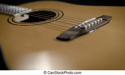 light yellow acoustic guitar close-up. Modern design, metal...