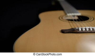 light yellow acoustic guitar close-up. Modern design, metal...