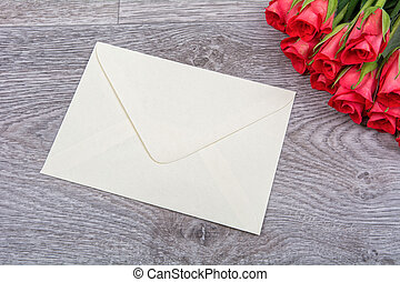 Light yellow envelope and roses on a wooden background