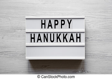 Lightbox with 'Happy Hanukkah' word over white wooden background, overhead view. From above, flat-lay, top view.