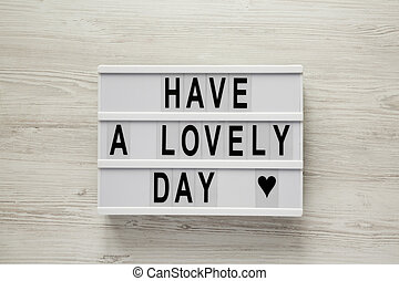 Lightbox with text 'Have a lovely day' on a white wooden background, top view. From above, flat lay, overhead. Closeup.