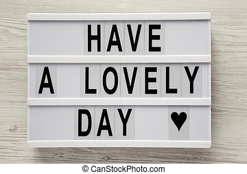 Lightbox with text 'Have a lovely day' on a white wooden surface, top view. From above, flat lay, overhead. Close-up.