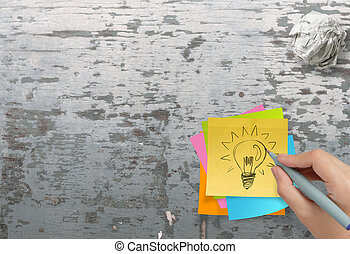 lightbulb as creative on crumpled sticky note paper on texture desk as concept
