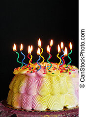 Lighted Birthday Cake - Lighted candles on a pink and yellow...