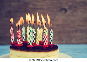 lighted birthday candles on a cheesecake, with a retro effect