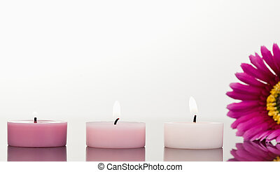 Lighted candles and a pink gerbera