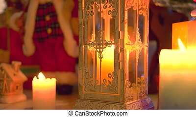 Lighted candles, gifts and Christmas ornaments.