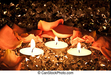 Lighted candles on a golden background with rose petals.