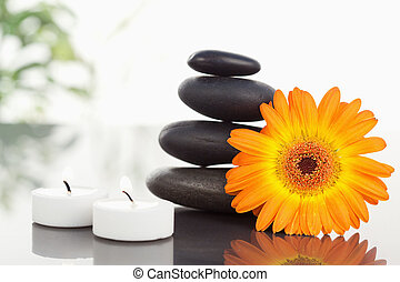 Lighted candles pebble stack an orange gerbera
