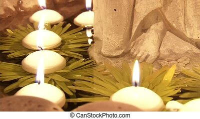 Lighted candles slowly float through the water in the temple