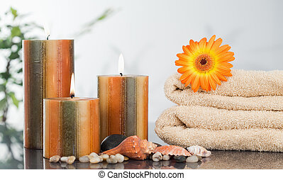 Lighted candles with an orange gerbera on towels and sea shells