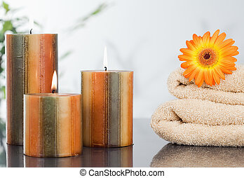 Lighted candles with an orange gerbera on towels