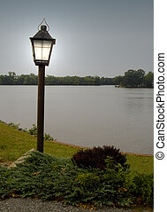 Lighted Lamp Post - Lamp post by a lake at dusk.