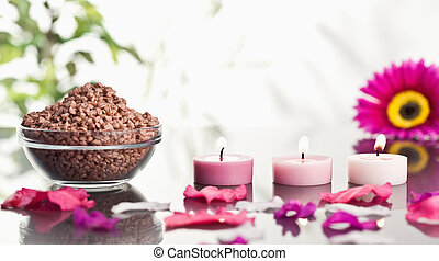 Lighted pink candles with petals and a bowl of gravel