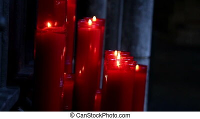 Lighted red candles in a dim-lighted place in church -...