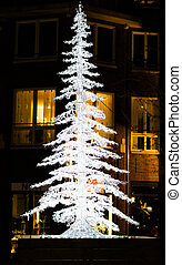 lighted up christmas tree decoration in the city streets at night