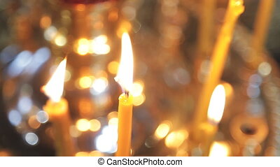 Lightened wax candles stand in church indoors on on sunday...