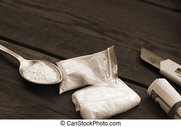 Lighter and spoon full of white powder on wooden background. Heroin drug addiction concept
