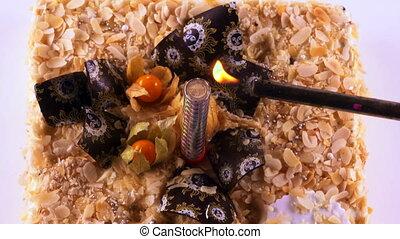 Lighter lights the firework sparkling candle on festive birthday dessert cake