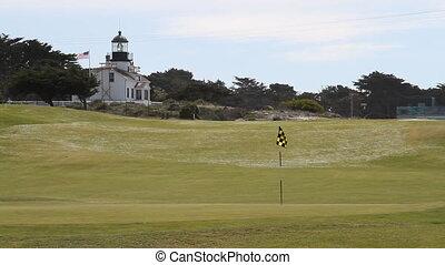 lighthouse an American flag on golf course