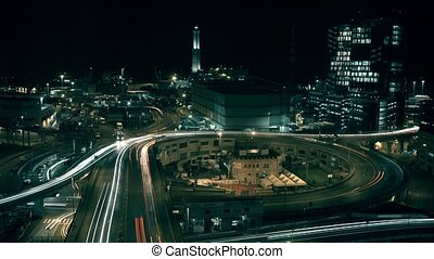 Lighthouse and city interchange traffic in seaport area of Genoa, Italy, at night. Long exposure time lapse