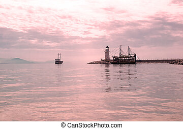 Lighthouse and sail ships in the Mediterranean sea at sunset