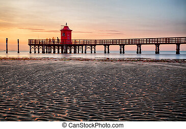 Lighthouse at sunset in Italy with beach