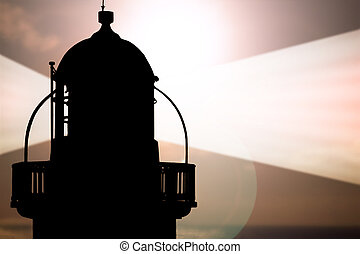 lighthouse captured with the sun behind it and beams on