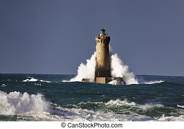 """Lighthouse called """"Le phare du four"""" in Tremazan in Brittany, France during storm in November"""