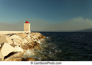 Lighthouse in the harbor of a of a small town on a stormy day - Croatia, island Brac