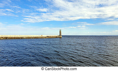 Lighthouse on a calm sea. White clouds in the sky.