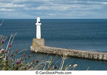 Lighthouse on a sunny day, against a stormy sky