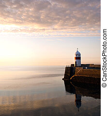 Lighthouse on breakwater wall with calm sea during sunrise....