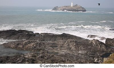 Lighthouse on island waves breaking