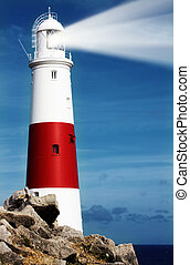 Lighthouse on rocks with lightbeam on Portland