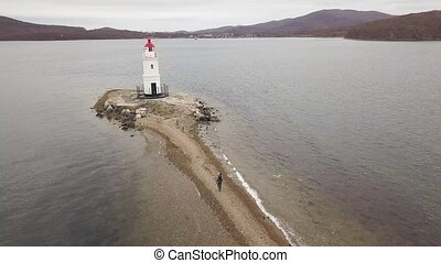 Lighthouse on sea coast view from flying drone. Aerial...