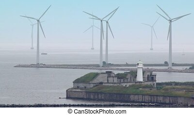 lighthouse on shore and windmills which produce electricity...