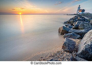 Lighthouse on the Dutch coast near the island of 'marken' during sunrise on a large inland lake