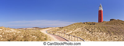 A footpath leading towards the lighthouse of the island of Texel in The Netherlands on a sunny day.
