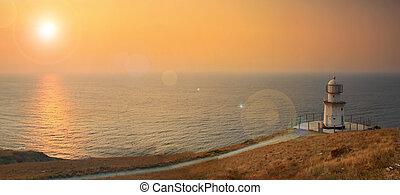 Lighthouse on the ocean beach at sunrise