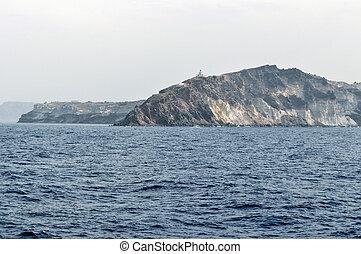 Lighthouse on the rocky shore of Santorini.