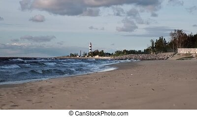 Lighthouse on the sandy Seashore in parturny and windy weather. Waves at sea with cloudy sky.