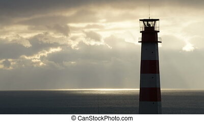 Lighthouse on the sea under stormy clouds at sunset