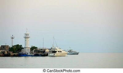 Lighthouse on the shore - Several ships off from behind the...