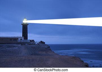 Lighthouse searchlight beam through foggy air. Punta Jandia...